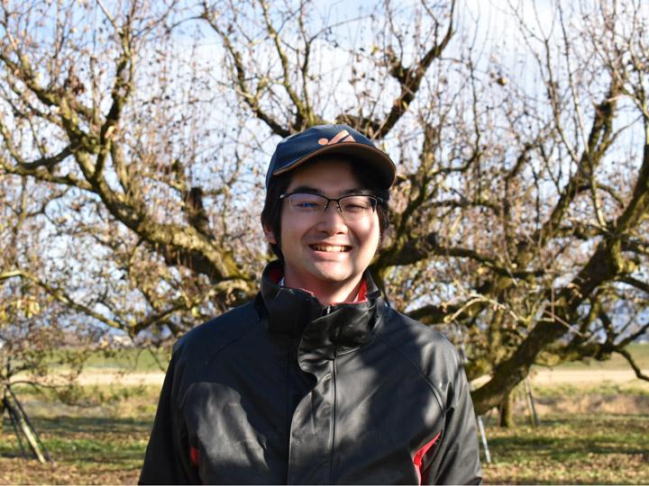 自身の果樹園でほほ笑む中村さん