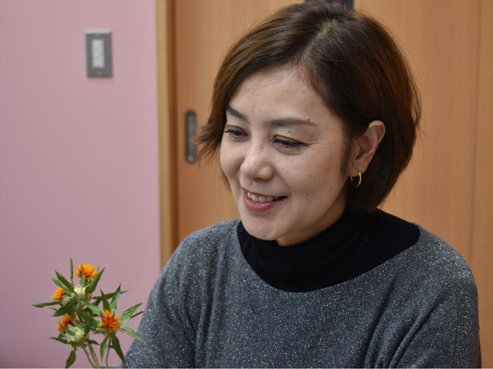 紅花のドライフラワーを見つめる海藤さん