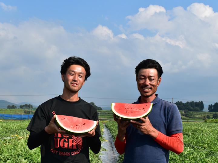 「スイカならどこにも負けませんよ」と自身の畑の前で笑顔の菅野さん(右) 高橋さん(左)