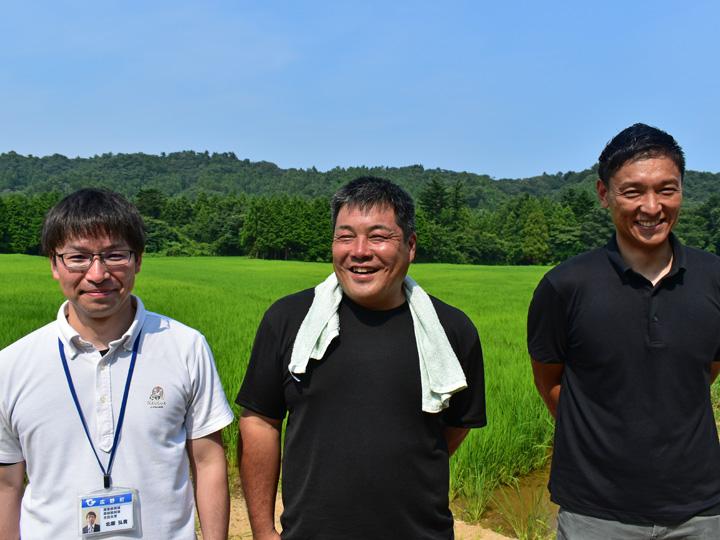福島県広野町の自身のほ場前で行政担当者と笑顔で写る横田さん