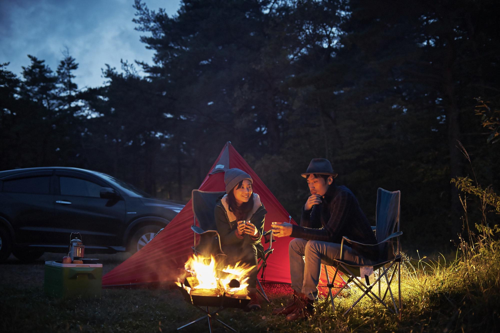焚き火の前で話すカップルイメージ