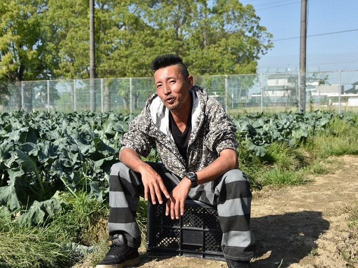 ブロッコリー畑で取材に応じる和想農園のワソ(谷和洋)さん