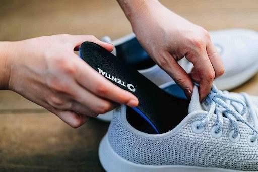 テンシャルのインソールを靴に設置する人