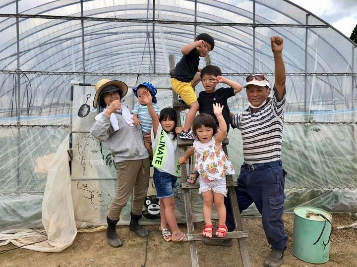 ハウスで記念撮影する菊川さん